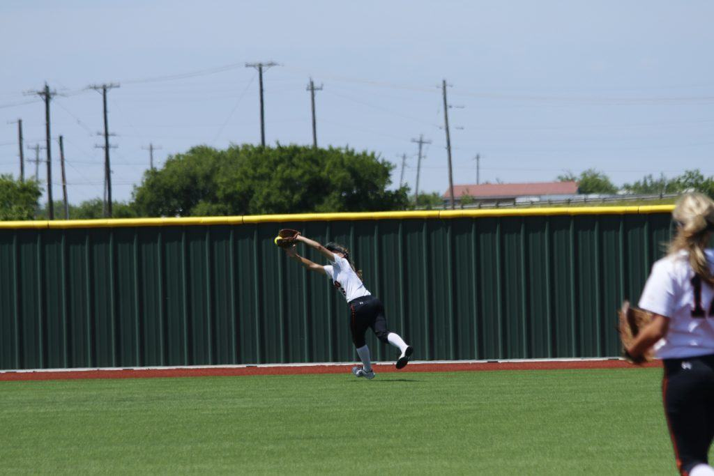 Aledo left-fielder Lindsey McElroy leaps to make a catch in the fourth inning of the Ladycats' 3-1 loss to Birdville Saturday at Eaton High School. (Photo by David Andrews)