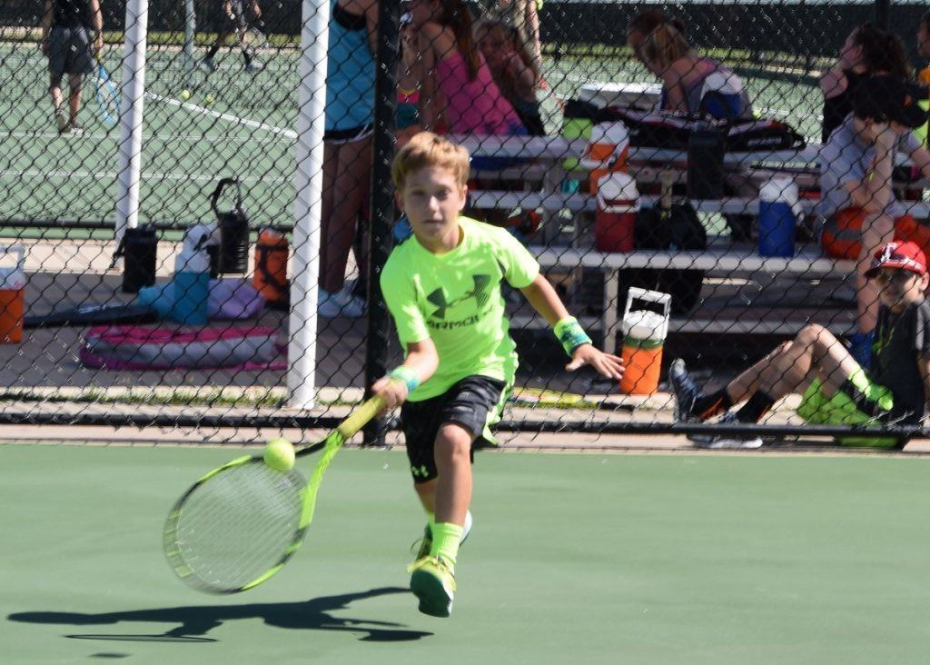 Jaren Scarborough hustles to get to a ball as he begins a forehand volley Monday morning at AHS Tennis Camp.
